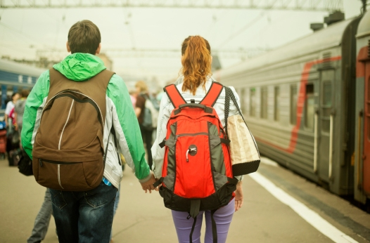 Caucasian couple holding hands on train station platform